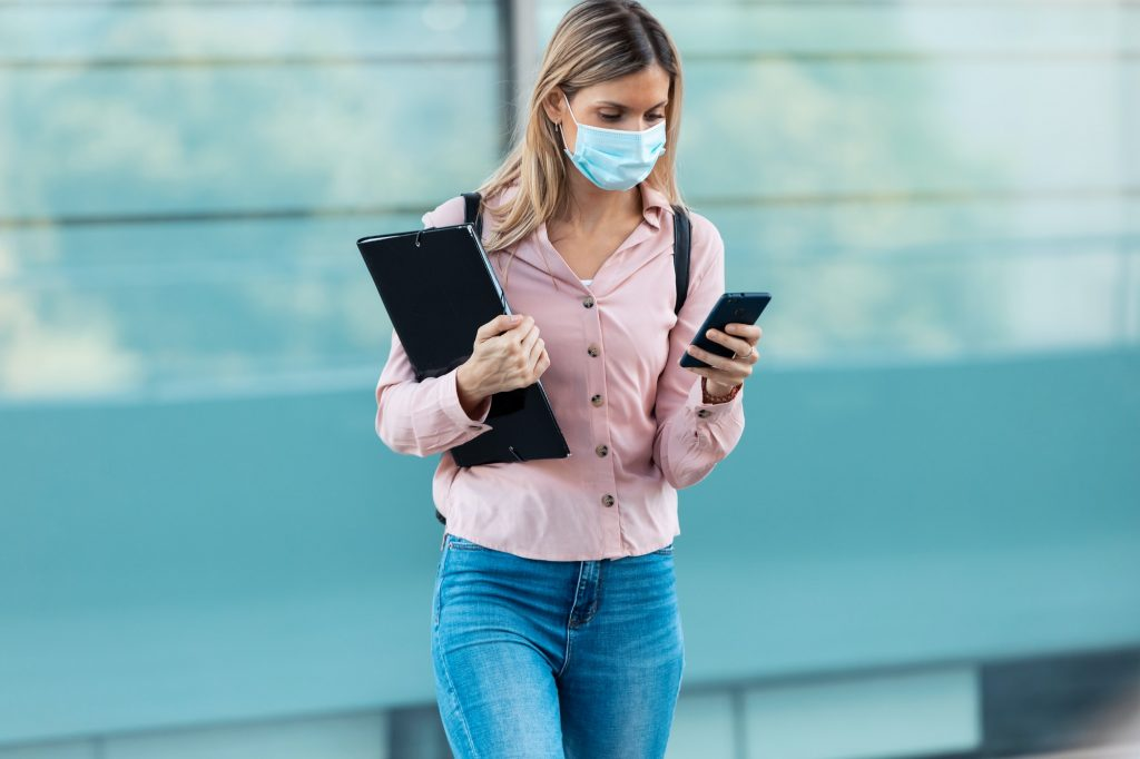Beautiful blonde woman in face mask using her mobile phone while walking in the street.