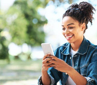 Happy Black Girl Using Mobile Phone App Sitting Outside
